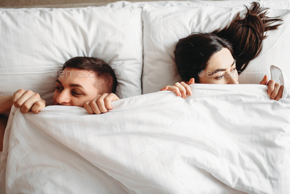 Shy love couple lies on big white bed, top view - Stock Photo - Images