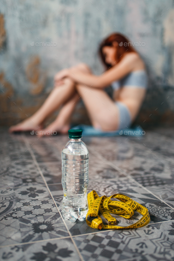 Water and measuring tape against anorexic woman - Stock Photo - Images
