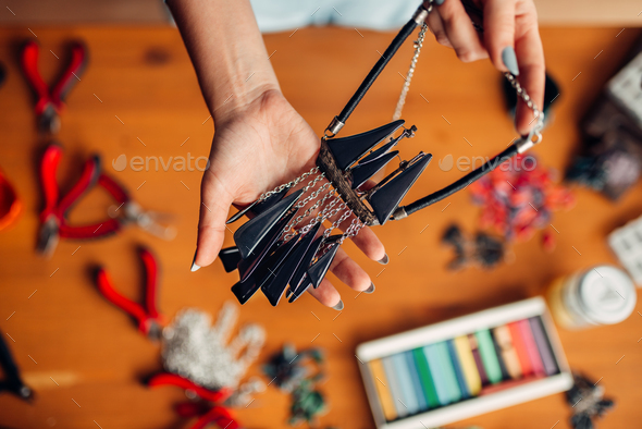 Female person holds handmade necklace, needlework - Stock Photo - Images