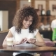 Portrait of a Mulatto Girl in a Coffee House. Beautiful Hispanic Woman Messaging on Smartphone and - VideoHive Item for Sale