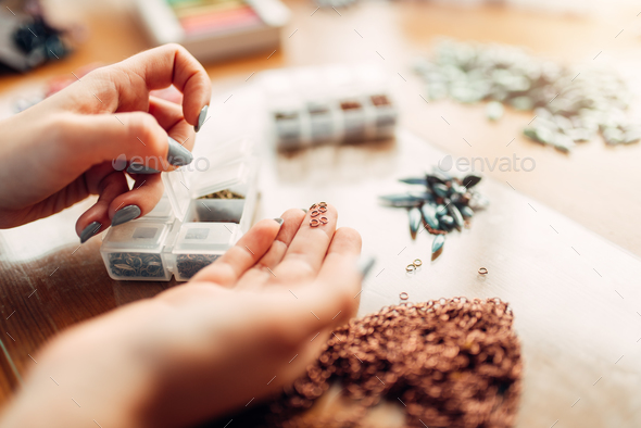 Female hands holds little metal rings, needlework - Stock Photo - Images