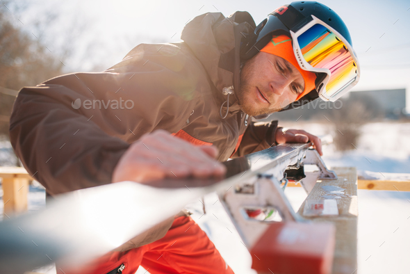 Male skier checks skis before skiing, winter sport - Stock Photo - Images