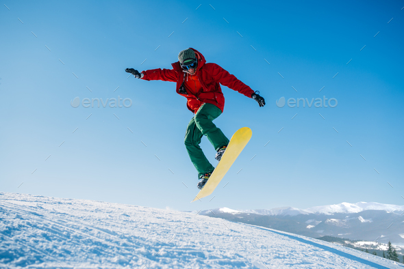 Snowboarder makes a jump on speed slope - Stock Photo - Images
