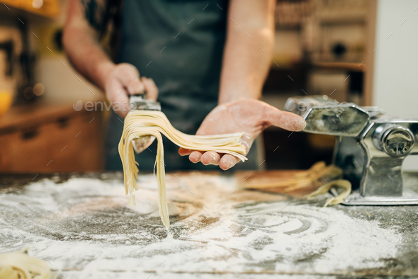 Chef cooking fettuccine in pasta machine - Stock Photo - Images