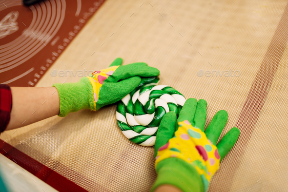 Kid hands in gloves making caramel sweets - Stock Photo - Images