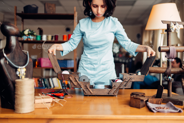 Needlework, female master at workplace in workshop - Stock Photo - Images