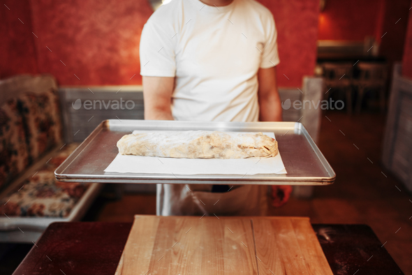 Chef holds metal baking sheet with apple strudel - Stock Photo - Images