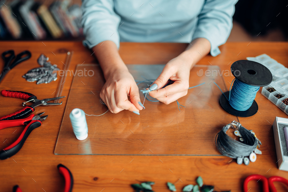 Female hands with pliers, top view, needlework - Stock Photo - Images
