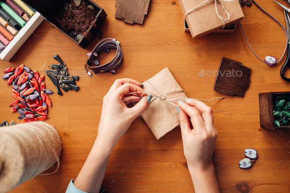 Female person tie a bow on a gift box, needlework - Stock Photo - Images