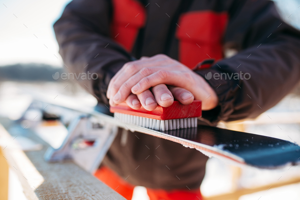Skier prepares his skis for riding, winter sport - Stock Photo - Images