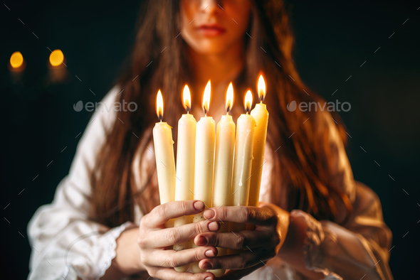 Female person holds candles in hands, divination - Stock Photo - Images