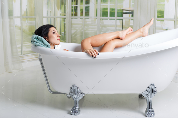 Beautiful young woman taking care about legs lying in the bathtube in the bathroom - Stock Photo - Images