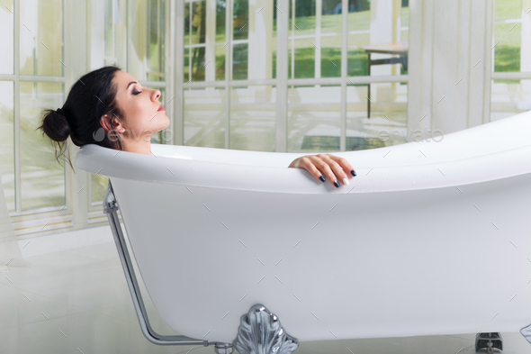 Bathing woman relaxing in bath smiling relaxing with eyes closed. - Stock Photo - Images