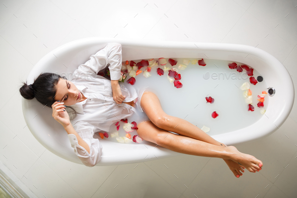 A young brunette woman takes a milk bath. - Stock Photo - Images