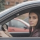 Beautiful Brunette Woman Sits in a Car on a Driver's Seat in the City - VideoHive Item for Sale