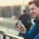 A Young Man Uses a Mobile Phone at Sunset in the City - VideoHive Item for Sale