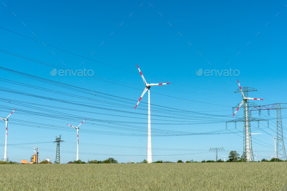 Wind engines and power supply lines on a sunny day - Stock Photo - Images