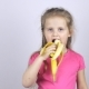A Young Girl Bites a Banana and Shows Her Thumb Up - VideoHive Item for Sale