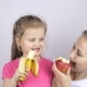 Young Mother with Her Daughter Smiling and Eating Banana and Apple - VideoHive Item for Sale