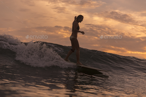 Surfer girl in ocean at sunset time - Stock Photo - Images