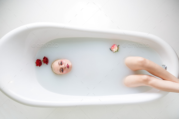 Beautiful young woman taking bath with milk - Stock Photo - Images