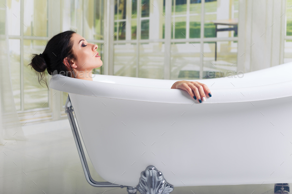 Bathing woman relaxing in bath smiling relaxing with eyes closed - Stock Photo - Images