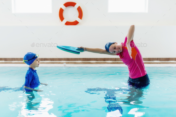 Boy having a swimming lesson with instructor - Stock Photo - Images