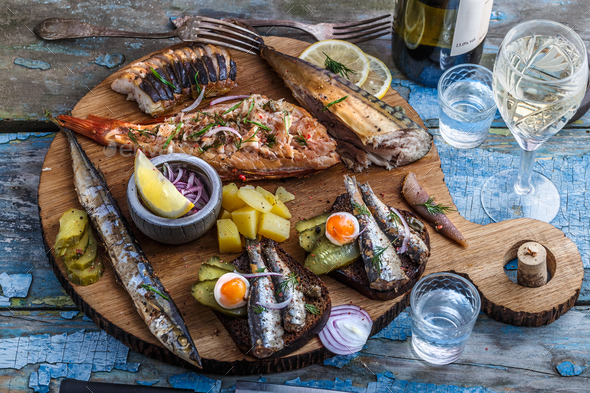 Smoked fish appetizers with mackerel, sturgeon, perch on woden cutting board - Stock Photo - Images