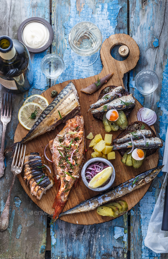Assorted smoked fish on wooden cutting board, top view - Stock Photo - Images