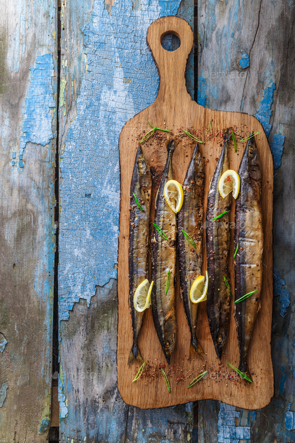 Smoked oceanic saury on wooden cutting board, top view, copy space - Stock Photo - Images
