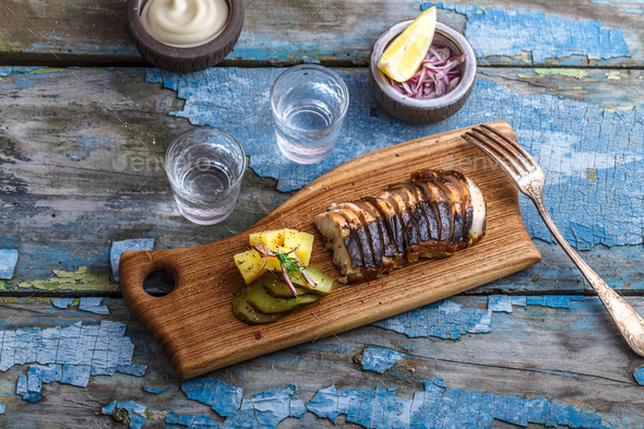 Pieces of smoked sturgeon on a cutting board - Stock Photo - Images