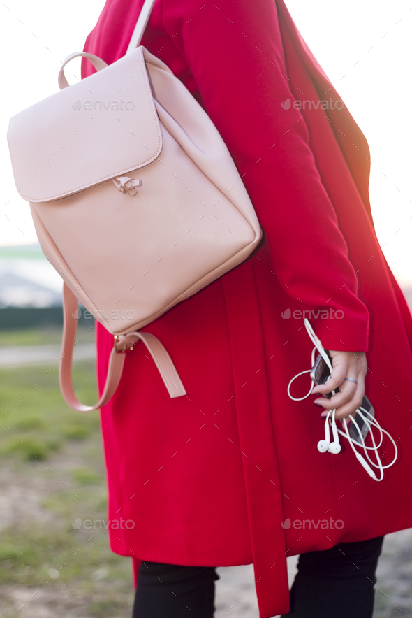 big pink backpack and phone with headphones in the arm of the girl in a fashionable red coat - Stock Photo - Images