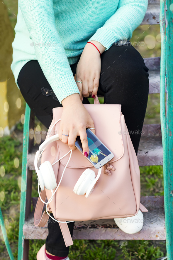 Women's legs in jeans and sneakers, backpack, headphones and smart phone - Stock Photo - Images