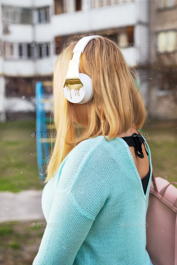 Girl with headphones and backpack on background of old houses. - Stock Photo - Images