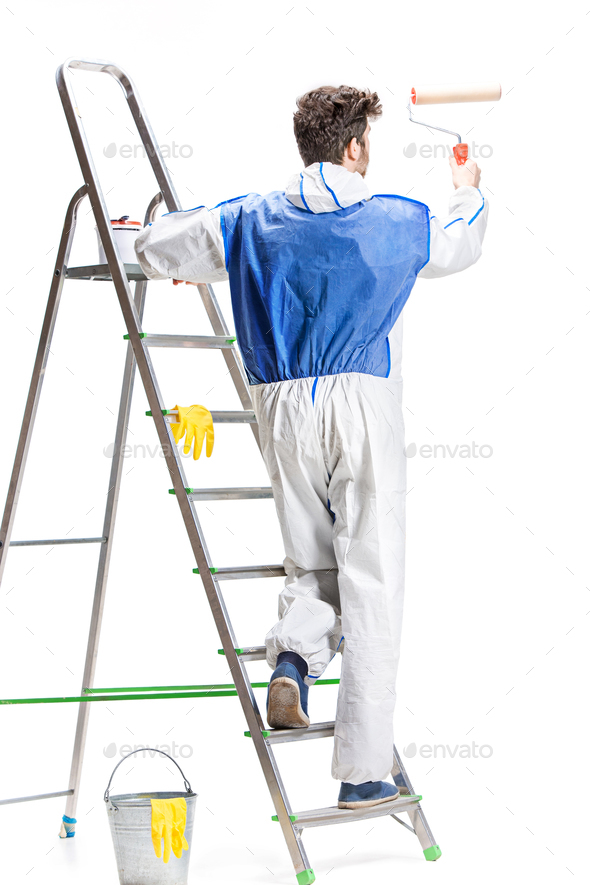 Young male decorator painting with a paint roller climbed a ladder isolated on white background. - Stock Photo - Images