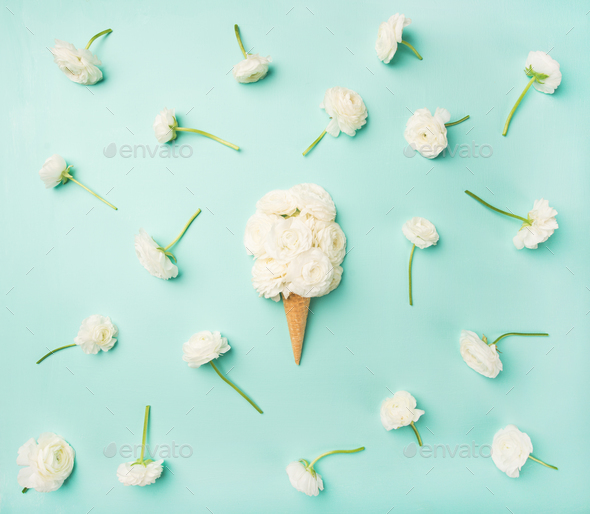 Waffle cone with white buttercup flowers over blue background - Stock Photo - Images