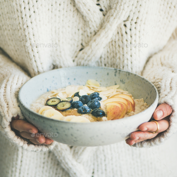 Woman in sweater holding bowl of oatmeal porriage, square crop - Stock Photo - Images