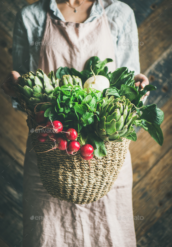 Female farmer holding basket of fresh garden vegetables and greens - Stock Photo - Images