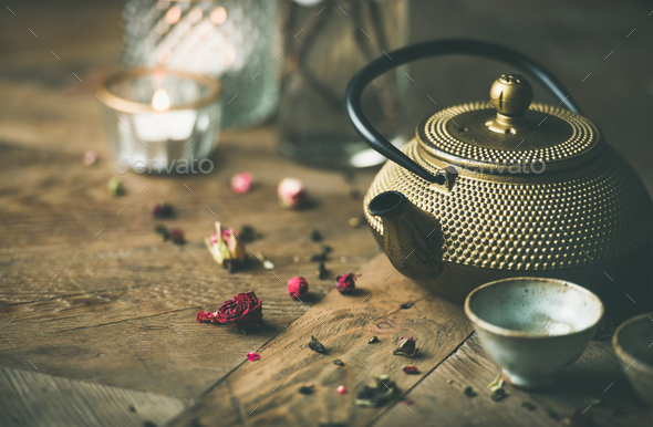 Golden iron teapot, cups, dried rose, candles over wooden background - Stock Photo - Images