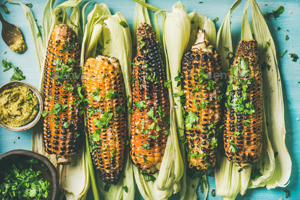 Flat-lay of grilled sweet corn with spices - Stock Photo - Images