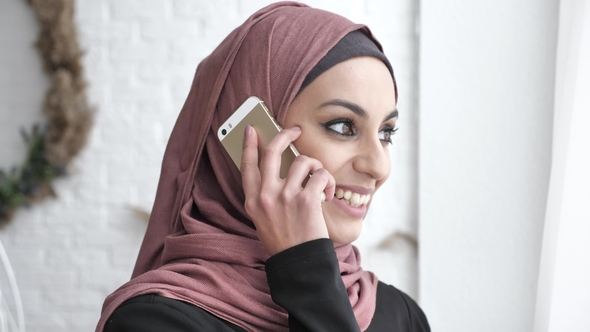 Young Beautiful Indian Girl in Hijab Looking Away, Looking at Camera,  Smiling, Talking on Smartphone by FootageUA