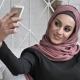 Young Beautiful Indian Girl Wearing Hijab, Smiling, Doing Selfie, Waving Her Hand, Greeting Gesture