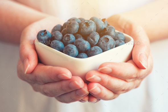Woman offering blueberry myrtilles - Stock Photo - Images