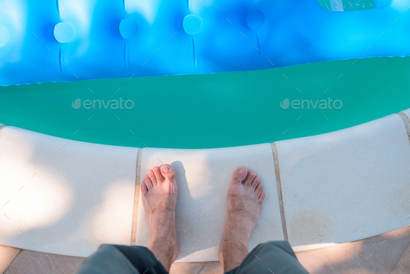 Bare male feet by the poolside - Stock Photo - Images