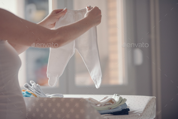 Mother sorting newborn baby clothing at home - Stock Photo - Images