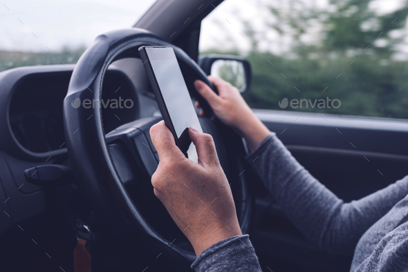 Woman simultaneously driving car and typing text message - Stock Photo - Images