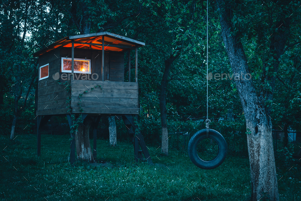 House on tree in evening garden - Stock Photo - Images