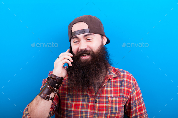 Happy man with long beard talking on the phone - Stock Photo - Images