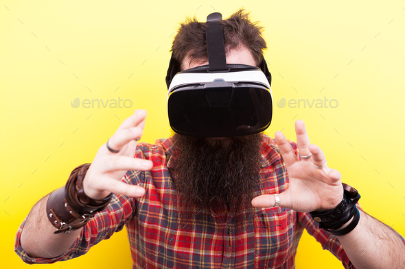 Long bearded hipster man wearing a virtual reality VR headset an - Stock Photo - Images