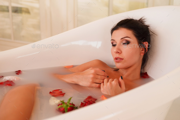 Young attractive woman relaxing in bath with foam and petals. - Stock Photo - Images